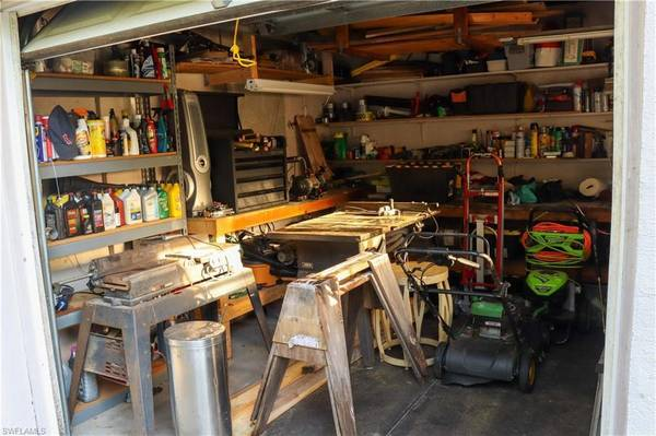 Photo Side of the home offers a large built in shed with workshop area. (Cape Coral, FL)