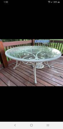 Photo Large round patio table, glass top, with iron umbrella stand - $200 (Wellington)